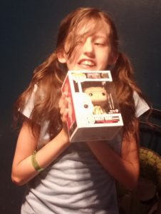 Harley with a Funko POP of her namesake, age 10